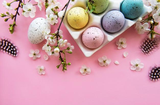 Vista superior de ovos de páscoa pintados e bandeja de ovos na superfície rosa