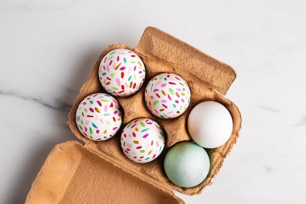 Vista superior de ovos de páscoa pintados na caixa