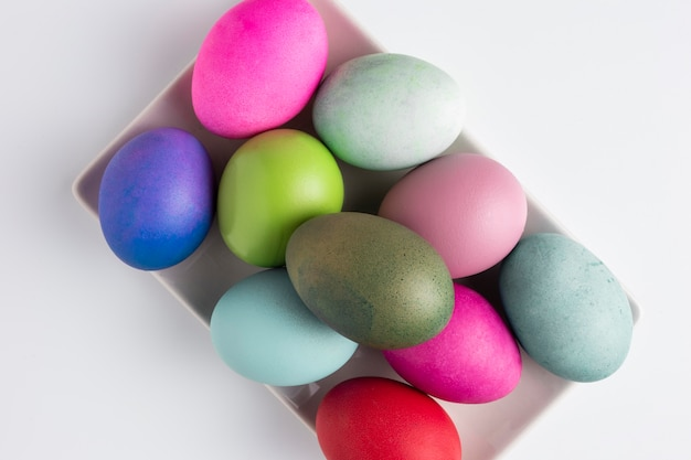 Vista superior de ovos de páscoa pintados no prato