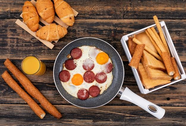 Vista superior de ovos fritos com torradas, croissants e suco na superfície de madeira escura horizontal