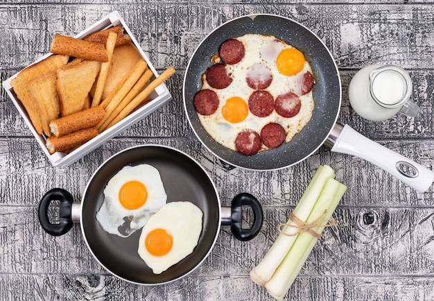Vista superior de ovos fritos com torradas na superfície branca horizontal