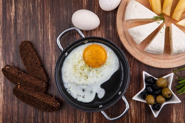 Vista superior de ovos fritos em uma frigideira com azeitonas e cebolinha, pão preto e queijo feta em um fundo de madeira