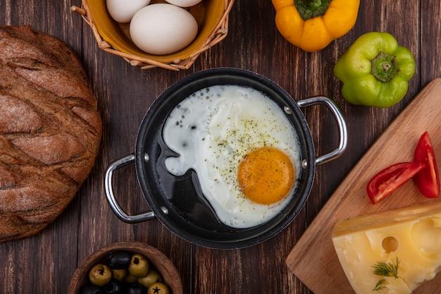 Vista superior de ovos fritos em uma frigideira com azeitonas, ovos de galinha em uma cesta e tomate de pimentão e maca de maasdam em fundo de madeira