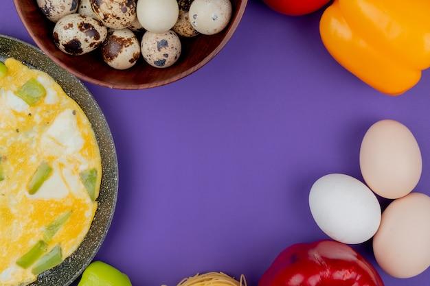 Vista superior de ovos fritos em uma panela com ovos de codorna em uma tigela de madeira sobre um fundo violeta com espaço de cópia