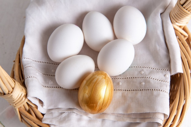 Vista superior de ovos inteiros brancos dentro da cesta com ovo dourado na superfície clara