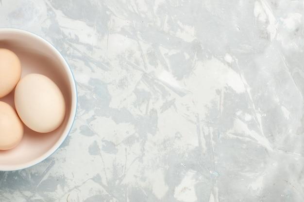 Vista superior de ovos inteiros crus dentro de um pequeno prato na mesa branca clara refeição com comida crua, foto de café da manhã