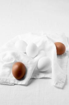 Vista superior de ovos marrons e brancos com toalha de cozinha