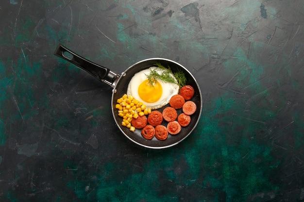 Vista superior de ovos mexidos com salsichas e verduras em fundo verde escuro