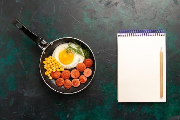 Vista superior de ovos mexidos com salsichas fatiadas e bloco de notas no fundo escuro