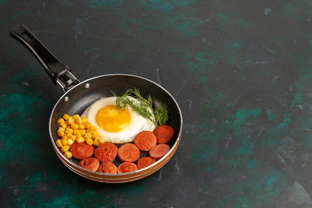 Vista superior de ovos mexidos com salsichas fatiadas e verduras dentro da panela no fundo escuro