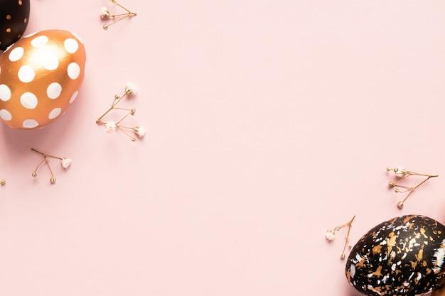 Vista superior de ovos pintados de madeira nas cores ouro, pretas e rosas com ramo de gypsophila em fundo rosa. feliz páscoa fundo