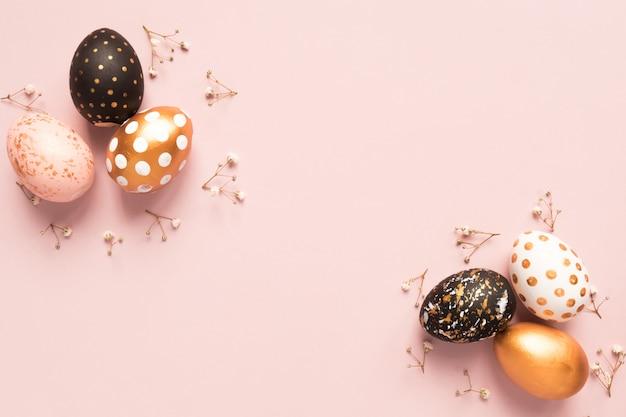 Vista superior de ovos pintados de madeira nas cores ouro, pretas e rosas com ramo de gypsophila em fundo rosa.