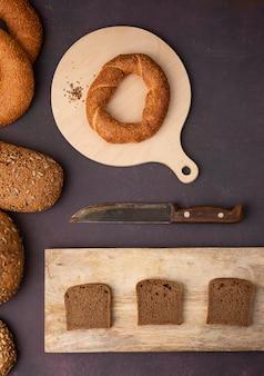 Vista superior de pães como bagel e pão de centeio fatiado em tábuas com faca no fundo marrom
