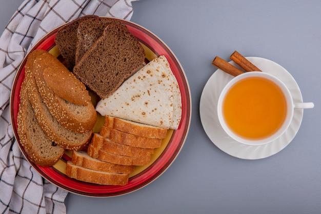 Vista superior de pães como baguete de centeio em fatias de sabugo marrom e pão achatado em um prato em pano xadrez e uma xícara de toddy quente com canela em pires em fundo cinza