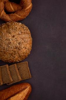 Vista superior de pães como baguete de espiga de pão e fatias de pão preto no lado esquerdo e fundo marrom com espaço de cópia