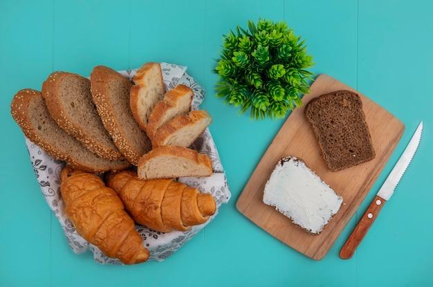 Vista superior de pães como baguete de sabugo fatiado e croissant em uma tigela e pão de centeio manchado com queijo na tábua de cortar com faca e planta no fundo azul