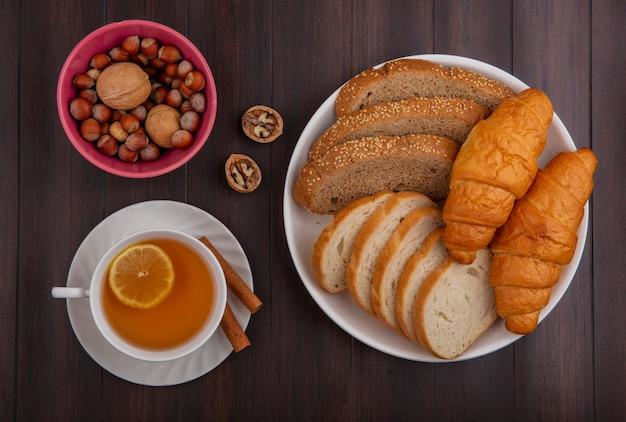 Vista superior de pães como baguete de sabugo marrom com sementes fatiadas e croissants em um prato e uma tigela de nozes nozes e uma xícara de toddy quente com canela no pires no fundo de madeira
