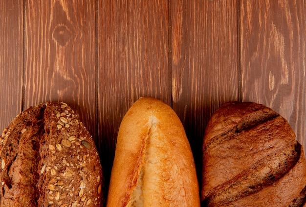 Vista superior de pães como baguete de sementes vietnamita e preta e pão preto na mesa de madeira com espaço de cópia