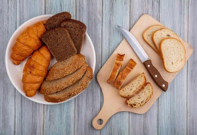 Vista superior de pães como baguete fatiada com faca na tábua e croissant de centeio e espiga marrom semeada em uma tigela com fundo de madeira