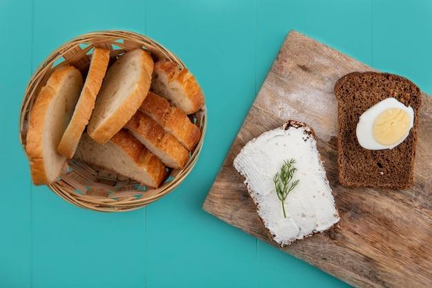 Vista superior de pães como baguete fatiada em uma cesta e uma fatia de pão de centeio untada com queijo e ovo em uma tábua de corte sobre fundo azul