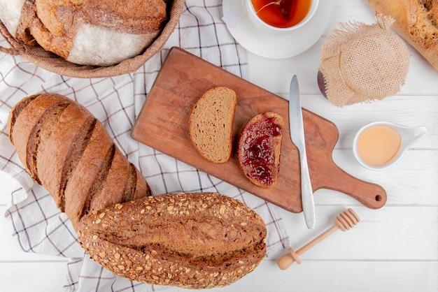 Vista superior de pães como baguete vietnamita preta semeada preta, espiga de pão preta e pão de centeio com geléia e faca na tábua com manteiga de chá na mesa de madeira