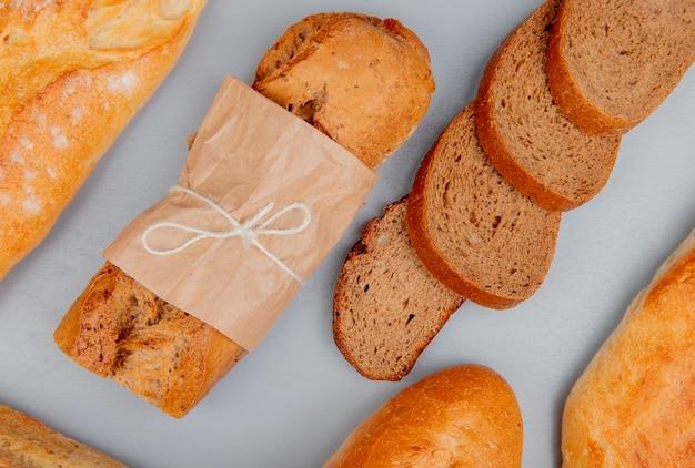 Vista superior de pães como baguetes crocantes de preto e brancas com fatias de pão de centeio na mesa azul