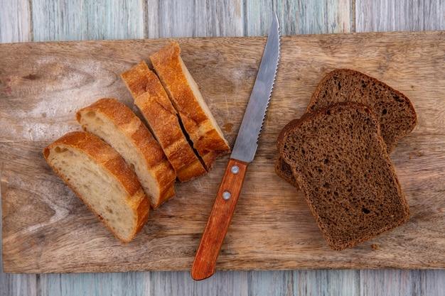 Vista superior de pães como baguetes fatiados e centeio com faca na tábua de corte no fundo de madeira