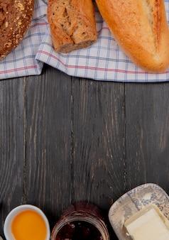 Vista superior de pães como baguetes pretos vietnamitas semeados no pano com manteigas e geléia na mesa de madeira com espaço de cópia