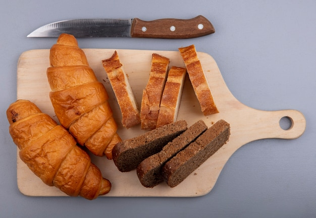 Vista superior de pães como croissant de centeio e baguetes na tábua e faca em fundo cinza