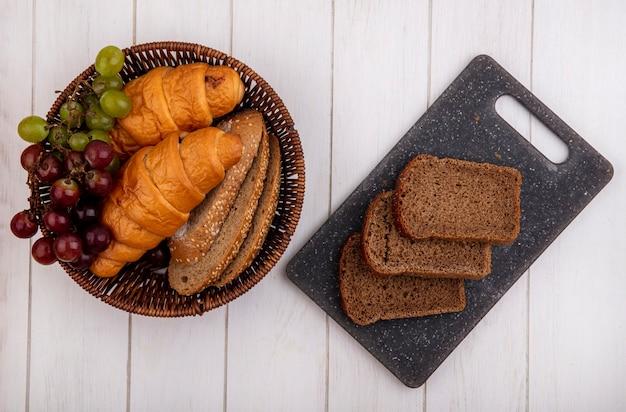 Vista superior de pães como croissant e fatias de pão de espiga de milho sem sementes com uva na cesta e fatias de pão de centeio na tábua com fundo de madeira