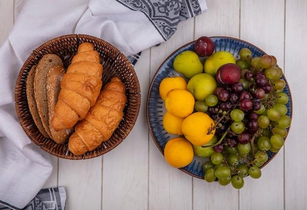 Vista superior de pães como croissant e fatias de pão de espiga de milho sem sementes na cesta em um pano e prato de pluot de nectacota de uva no fundo de madeira