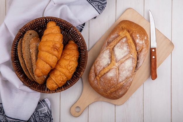Vista superior de pães como croissant e fatias de pão de espiga de milho sem sementes na cesta no pano e pão crocante na tábua de corte no fundo de madeira
