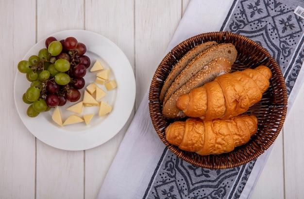 Vista superior de pães como croissant e fatias de pão de espiga de milho sem sementes na cesta no pano e prato de uva e queijo no fundo de madeira