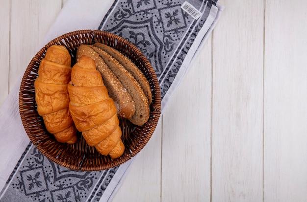 Vista superior de pães como croissant e fatias de pão de espiga marrom com sementes em uma cesta em um pano em um fundo de madeira com espaço de cópia