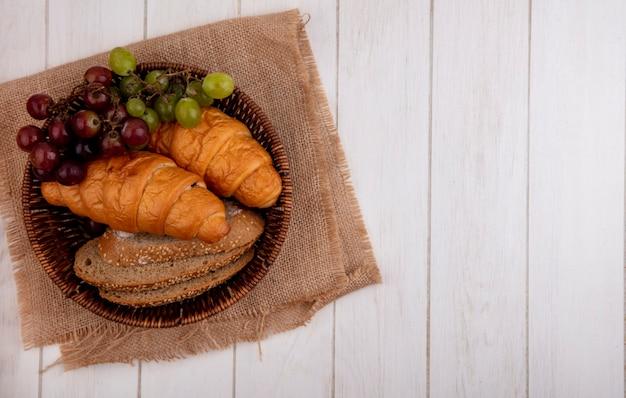 Vista superior de pães como croissant e fatias de pão de sabugo integral com uva em uma cesta em pano de saco em fundo de madeira com espaço de cópia