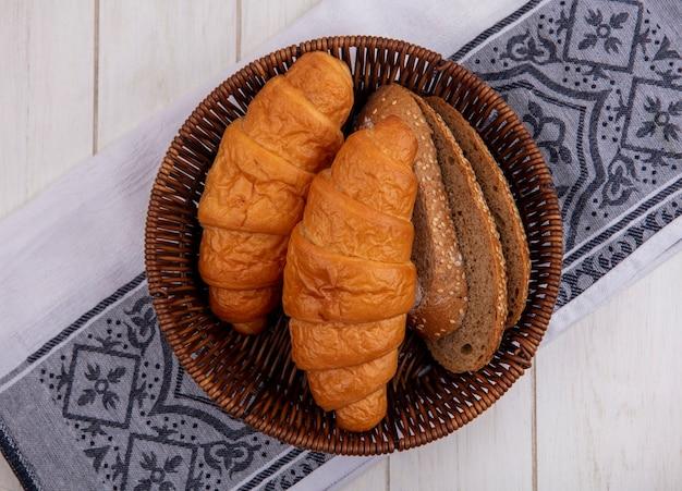 Vista superior de pães como croissant e fatias de pão de sabugo marrom com sementes em uma cesta em um pano com fundo de madeira