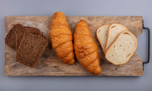 Vista superior de pães como croissant fatiado de centeio e baguete em uma tábua em fundo cinza