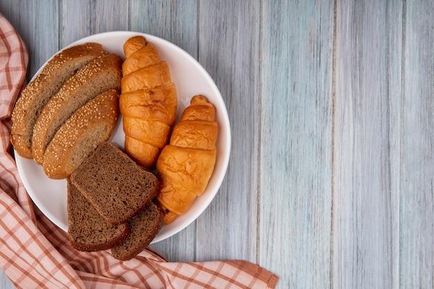 Vista superior de pães como croissant fatiado de centeio e espiga marrom semeada em prato sobre pano xadrez em fundo de madeira com espaço de cópia