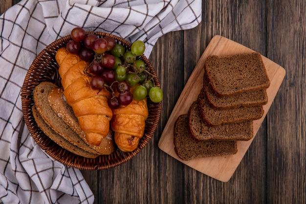 Vista superior de pães como croissants e fatias de pão de espiga de milho sem sementes com uva na cesta em pano xadrez e fatias de pão de centeio na tábua de corte em fundo de madeira