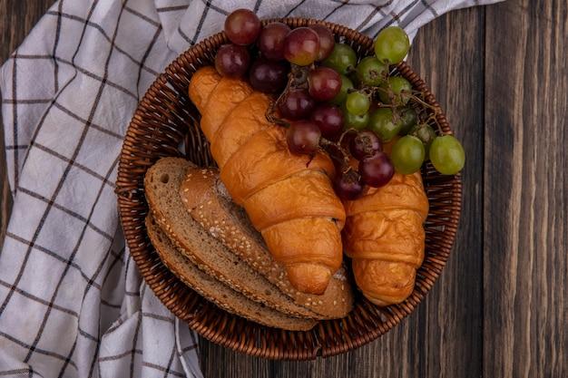 Vista superior de pães como croissants e fatias de pão de sabugo integral com uva em uma cesta em tecido xadrez em fundo de madeira