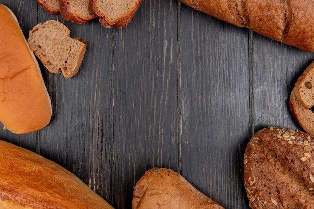 Vista superior de pães diferentes, como sanduíche de centeio baguete preto sobre fundo de madeira com espaço de cópia