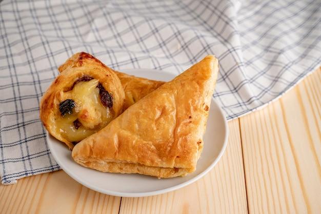 Vista superior de pães doces frescos e torta colocada em uma bandeja de madeira e guardanapo para o café da manhã.