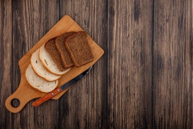 Vista superior de pães em fatias de centeio e brancos com faca na tábua de corte em fundo de madeira com espaço de cópia