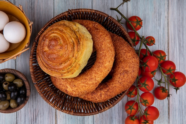 Vista superior de pães em um balde com azeitonas em uma tigela de madeira e tomates de videira isolados em um fundo cinza de madeira
