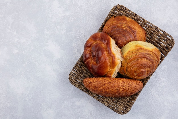 Vista superior de pães em um balde em um fundo branco com espaço de cópia