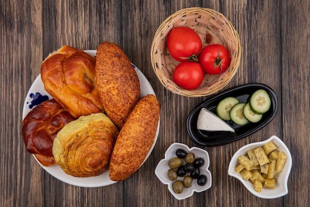 Vista superior de pães em um prato com tomates frescos em um balde com azeitonas em uma tigela sobre um fundo de madeira