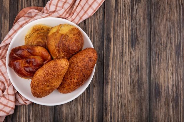 Vista superior de pães em um prato em um pano xadrez em um fundo de madeira com espaço de cópia