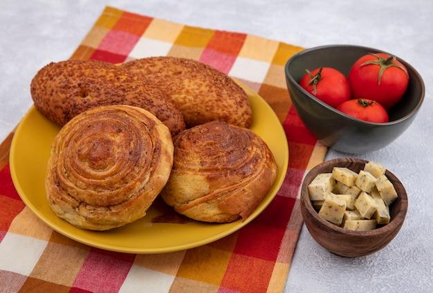 Vista superior de pães em uma placa amarela em um pano xadrez com queijo em uma tigela de madeira com tomates em uma tigela em um fundo branco Foto gratuita