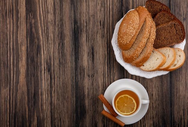 Vista superior de pães fatiados com sementes de centeio-espiga marrom e brancos no prato e xícara de toddy quente com canela no pires em fundo de madeira com espaço de cópia
