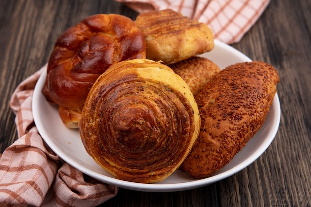 Vista superior de pães frescos, como gogals de hambúrgueres em um prato em um pano xadrez em um fundo de madeira com espaço de cópia